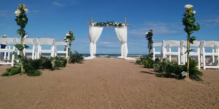 bamboo archway with white flowers with curtain material and tiki