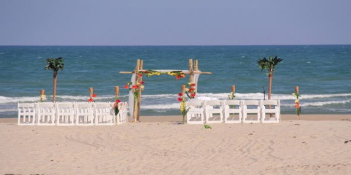 beach set up with bamboo archway with tropical flwoers3